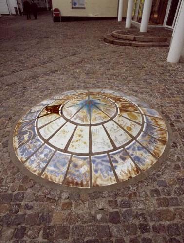 Fotograf: Eget fotoVærk  titel: Ymer Værk  type: Skulptur Materiale: Porcelænsklinker på beton Størrelse: Højde 0,5 m - diameter 2,30 m Færdiggjort: 1992 Placering: Randers Kommunes Kunstfond